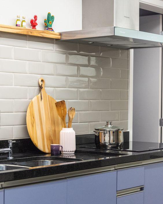 cozinha com subway tiles branco na parede da pia, armário azul e bancada da pia de granito preto