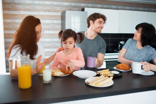 Счастливый завтрак большой семьи на кухне. братья и сестры, родители и дети,  мама и бабушка. отец и дочь. все едят по утрам, болтают и веселятся. |  Премиум Фото
