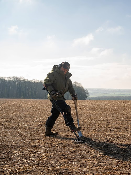 Peter Welch scanning a field with a metal detector