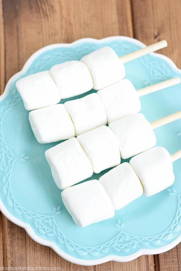 Insert lollipop or caramel apple stick into 3 large marshmallows. Begin melting chocolate over...
