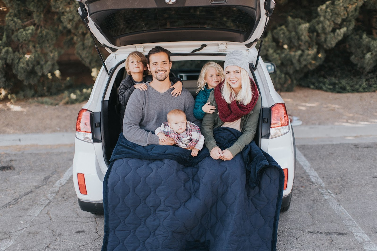 family sitting in rear of car with blanket