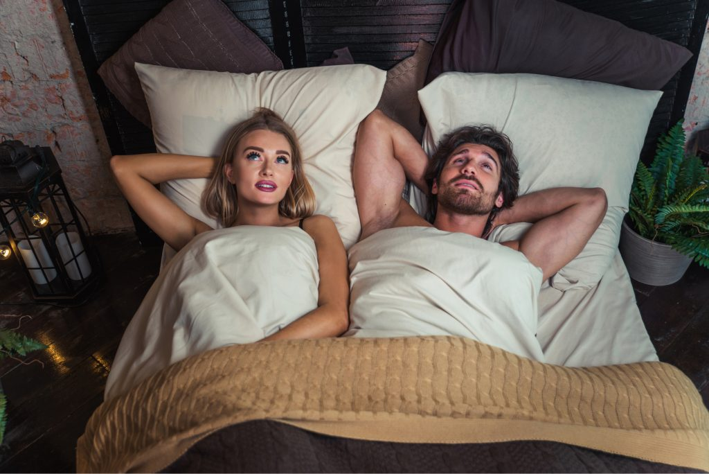 couple relaxing in bed after sex