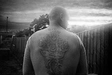 man met tatoeage, die hele rug vult, van rozen en een tekst