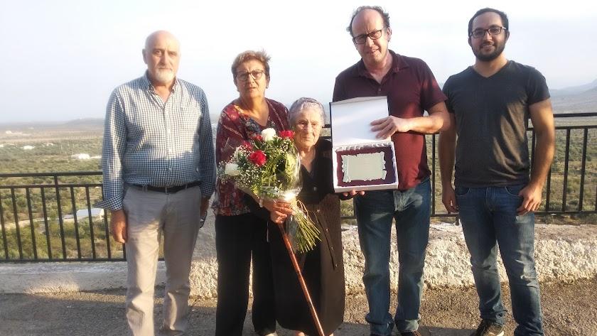 María Moreno junto a los concejales que le hicieron entrega de la placa y las flores.