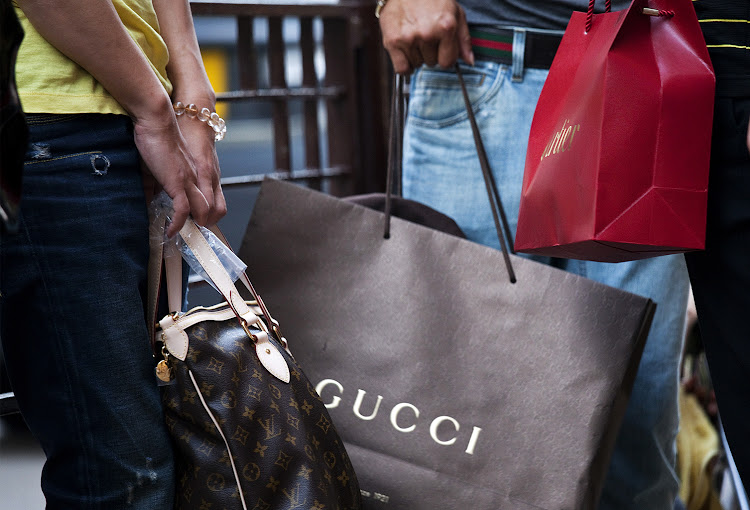 Shoppers hold bags from luxury stores Gucci, Louis Vuitton, and Cartier.