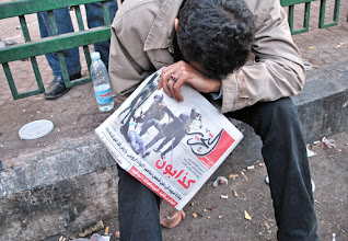 Photo: A young man crying after viewing the cover of 'Tahrir' with a copy still in his hands.