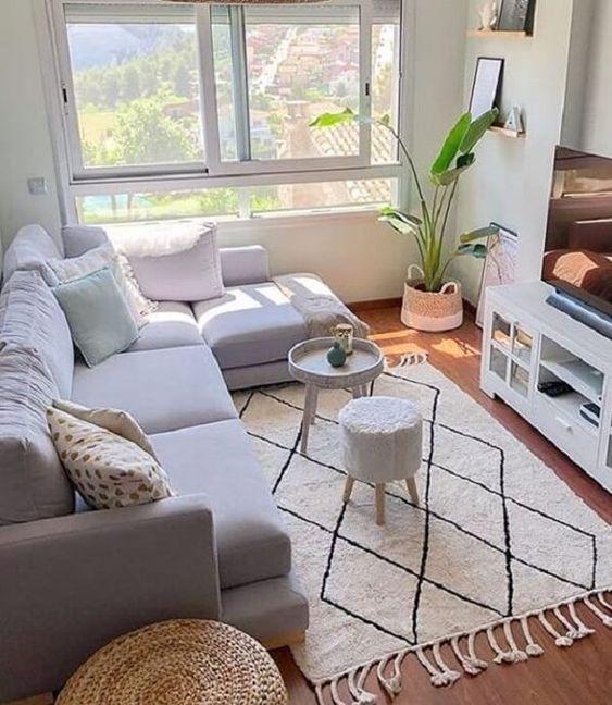Sala com sofá branco, plantas e mesinhas de centro. Hack branca com TV e prateleiras com quadros decorativos.