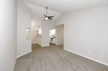 Living room with brown carpet, light gray walls, and ceiling fan