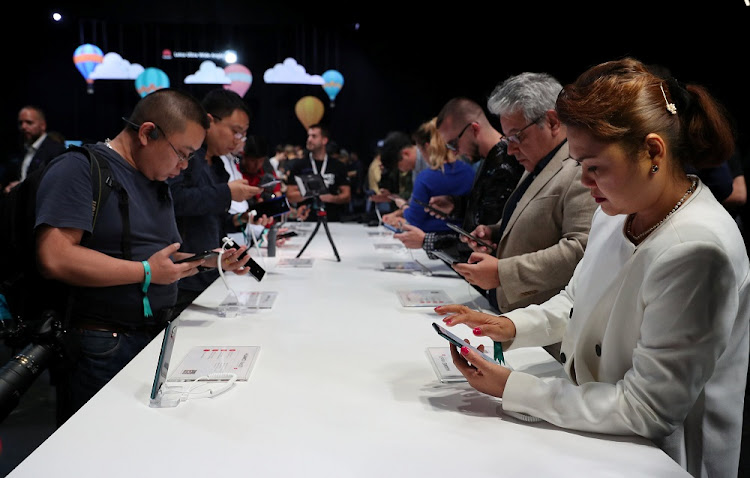 People look at display models of the Huawei Mate20 smartphone series at a launch event in London, Britain, October 16 2018. Picture: REUTERS/HANNAH McKAY