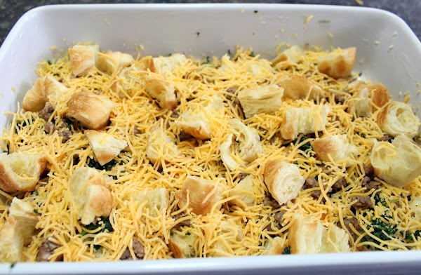 Croissants and cheese added to baking dish.