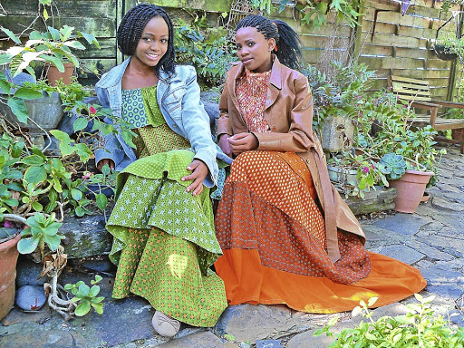 Familiar patterns: Yonela Mja, left, pairs a vintage isishweshwe dress with an oversized denim jacket, while her sister, Aviwe, complements her dress, in Da Gama Textiles's pumpkin shade, with a sleeveless knitted top and leather jacket. Picture: THE HERALD/SOLETTE RHODES