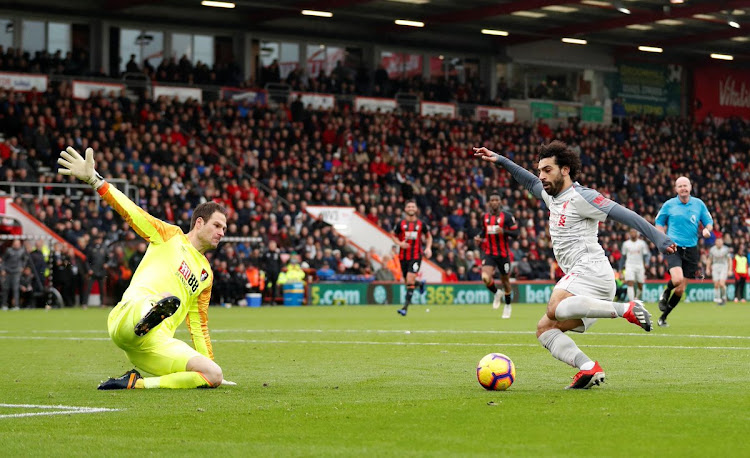 Liverpool Egyptian forward Mohamed Salah dribbles past the goalkeeper to score one of his three goals in a 4-0 Premier League win over Bournemouth on December 8 2018.