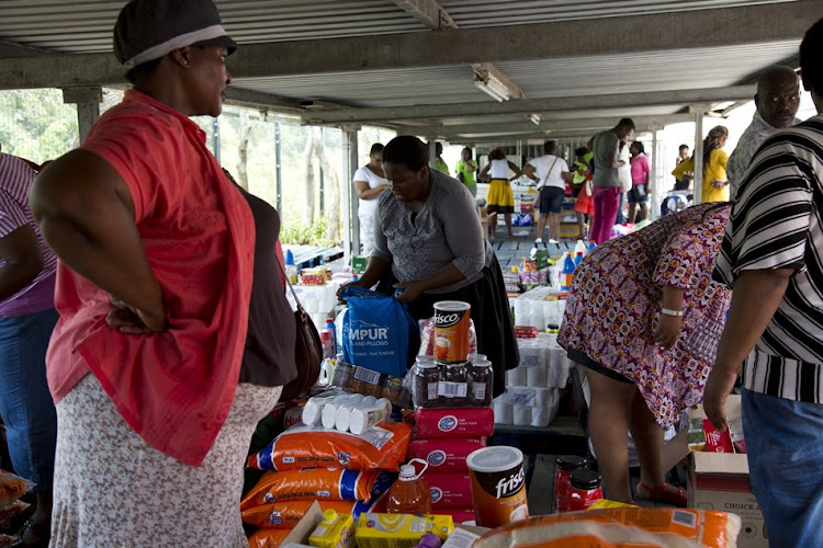 Stokvel members share out their joint purchases in the parking lot of a Makro store in Durban. Picture: ROGAN WARD