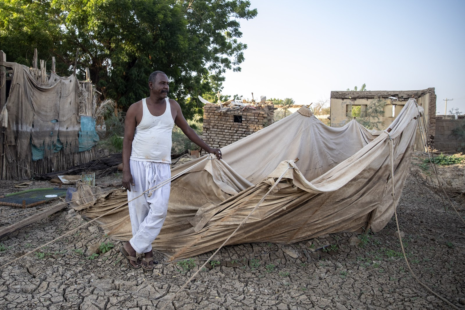 Nagy, one of the Wad Ramly villagers, next to his destroyed house and the tent he is living in after the floods