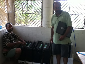 Photo: ADIRE Founder Dr D.P Kar with solar technician Madan Pati trying to charge the electic car Reva with solar panels