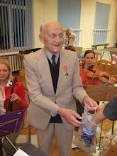 """Photo: """"Viskas prasidėjo 1961m., kai Povilas Bekeris įkūrė muzikos mėgėjų orkestrą ir suformavo jo, kaip klubo ir bendraminčių bendruomenės, viziją. Jau nuo pačių pradžių šis orkestras nebuvo tik orkestras, bet glaudi bendruomenė. ... Stengiamės išsaugoti pačią bendruomenės dvasią – pavyzdžiui, iki šiol per pertraukas gydytojas V. Gurevičius, vyriausias orkestro muzikantas, dalija visiems saldainius"""". Ištrauka iš straipsnio Muzikos surinkti, 2006-04-06, Rubrikose: Kultūra. Komentarai ir pokalbiai."""