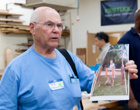 Photo: Bob Browning shows a picture of the lathe that he and Bert Bleckwenn built for the booth at the fair.