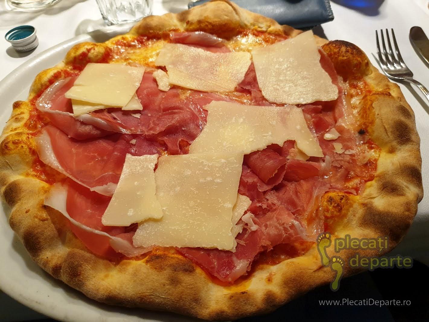 Pizza cu prosciuto si parmezan in Parma. parmigiano reggiano. Prosciuto și parmezanul sunt principalele ingrediente care se folosesc la pizza si in alte mancaruri traditionale italiene. bologna parma lugo obiective turistice mancaruri traditionale italia