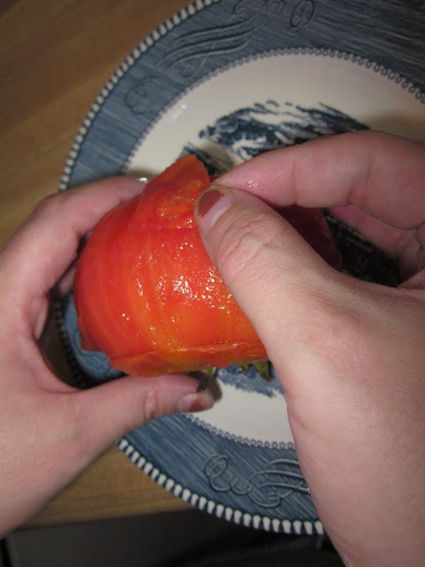 After about a minute, remove the tomatoes from the water and remove their skins....