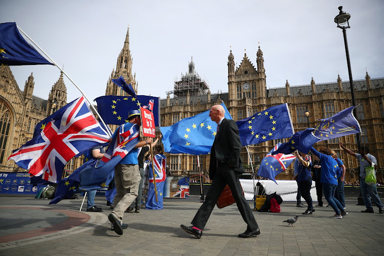 Anti-Brexit demonstrators wave flags outside the Houses of Parliament, in London, UK, on Monday.