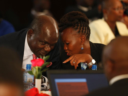 IEBC chair Wafula Chebukati (L) with former commissioner Roselyn Akombe consult with each other during the pre-nomination meeting for all presidential aspirants in Nairobi on May 23, 2017.