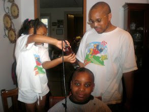 Photo: Kaleya helps to cut Miles' hair