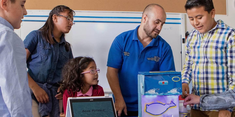 Un profesor se encuentra junto con sus estudiantes mirando un proyecto de tecnología.