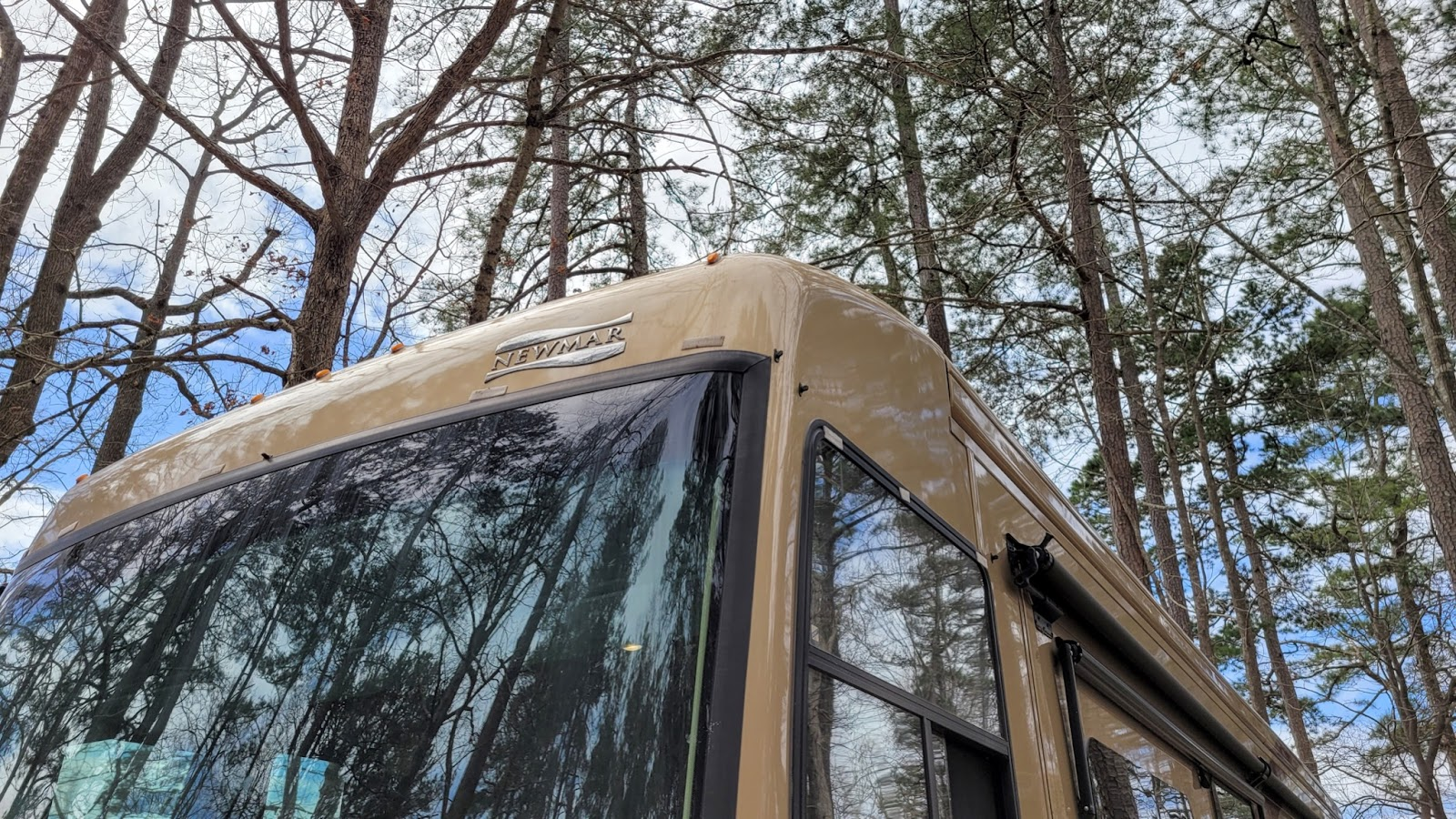 Top of a Class A RV parked in a woodsy campsite
