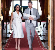 The Duke and Duchess of Sussex pose with their newborn son. Archie in St George's Hall at Windsor Castle on May 8 2019.