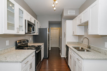 Cottonwood floorplan fully-equipped kitchen with granite countertops, white cabinets, and stainless steel appliances