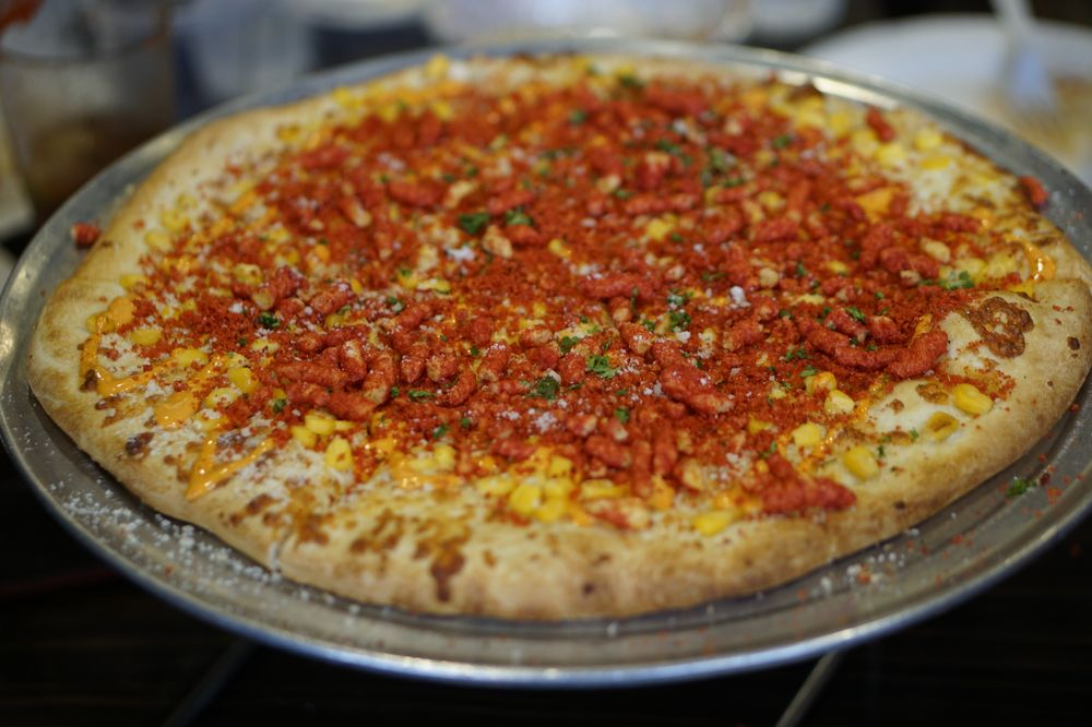 Photo of elote (corn) pizza with Hot Cheeto dusted on top.