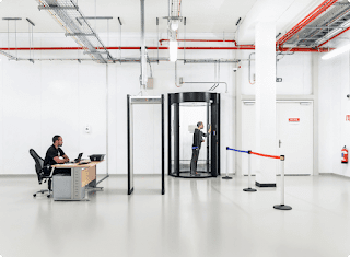Interior of a Google Cloud data center showing a security guard and another person going through a secure entry that requires multiple layers of security protocols.