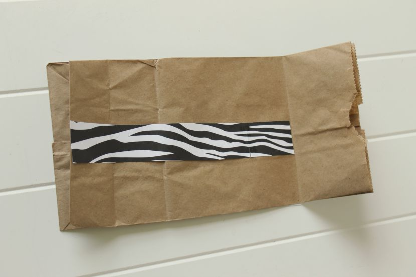 Glue a strip of animal-print scrapbook paper along the back crease of your paper bag, from the bottom of the bag to just below the fold.