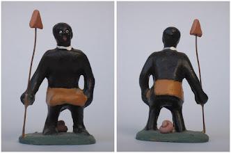 Photo: núm. 0016, El Negre de Banyoles, autoria: Anna Ma Pla, any, 2000, altura 7,7 cm. Es realitzà arran de la denúncia  d'un metge d'origen haitià resident a Catalunya, Alphonse Arcelin,  per l'exposició d'un guerrer boiximà  dissecat i exposat al Museu Darder de Banyoles.  L'incident va atreure l'atenció dels mitjans de comunicació els quals van donar a conèixer àmpliament la notícia; finalment l'humà dissecat es retornà a Botswana per ser enterrat dignament.