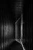 lijnenspel van gang met verticale planken wanden waar aan eind wat licht binnenvalt
