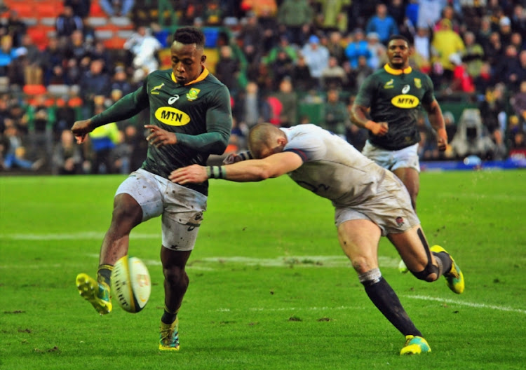 The Cell C Sharks winger S'Busiso Nkosi kicks the ball away from an England player during the Castle Lager Incoming Series match between South Africa and England at DHL Newlands on June 23, 2018 in Cape Town, South Africa.