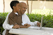 A grandfather and grandson working together on a laptop.