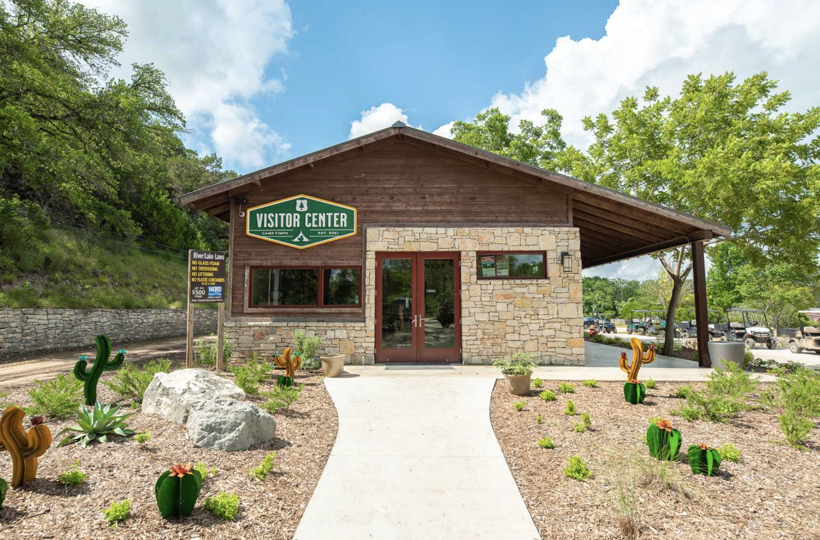 Visitor Center at Camp Fimfo campground with blue skies and green trees