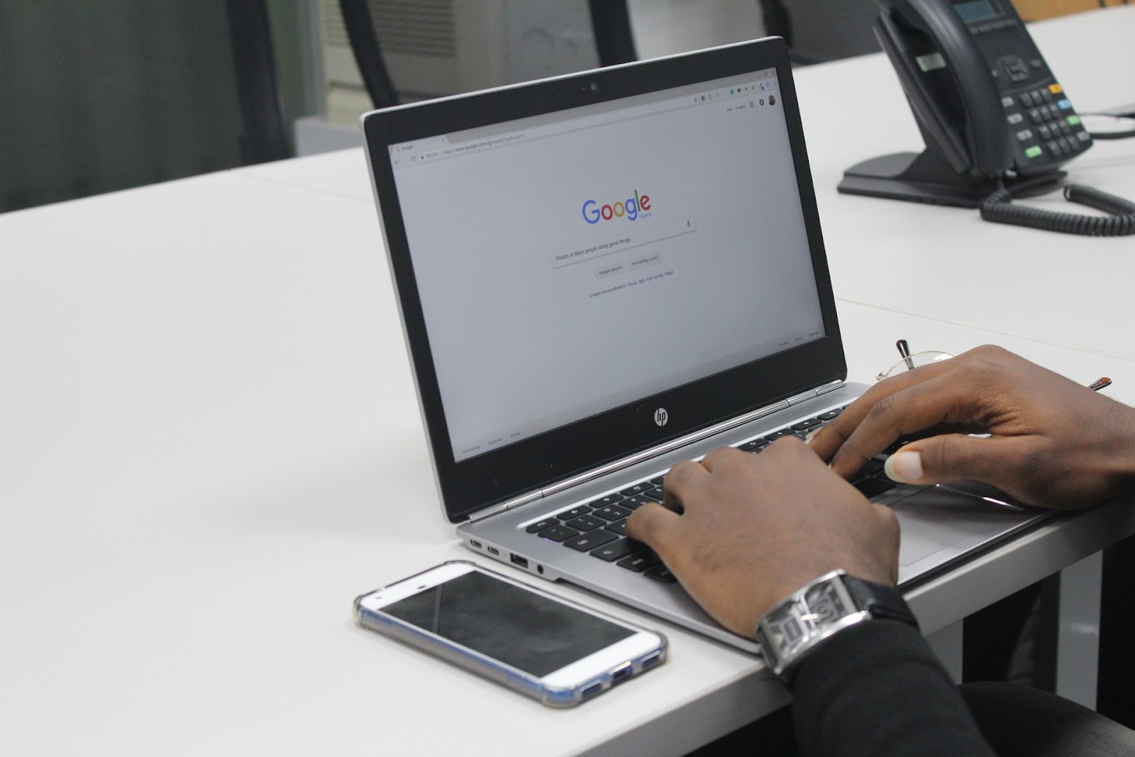 a person's hands typing on an HP laptop with a Google browser open, and an iPhone on the table next to it