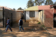 Local children walk past the murder scene where  intelligence police officer Ntobeko Nhlanhla Langa was shot dead  in  White City, Soweto. /Thulani Mbele