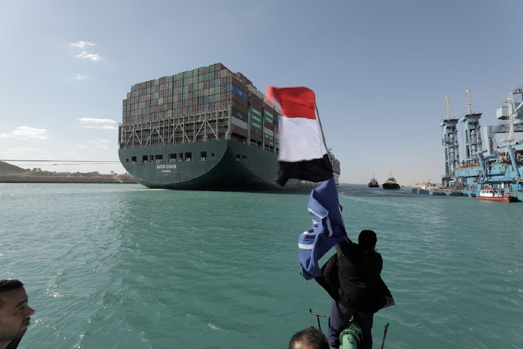 A man waves an Egyptian flag as ship Ever Given, one of the world's largest container ships, is seen after it was fully floated in the Suez Canal in Egypt. Picture: SUEZ CANAL AUTHORITY/HANDOUT via REUTERS