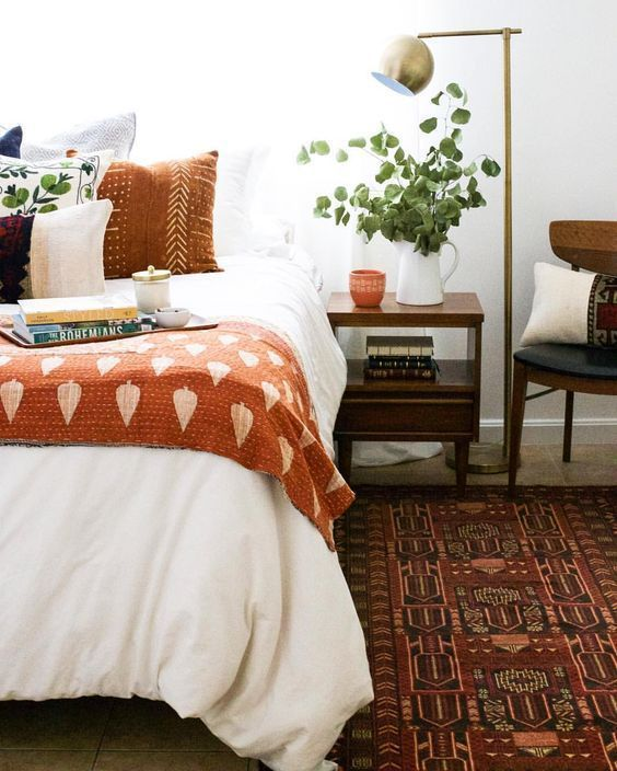 Fall bedroom decor bedroom setting with orange throw on the bed and orange pillows.