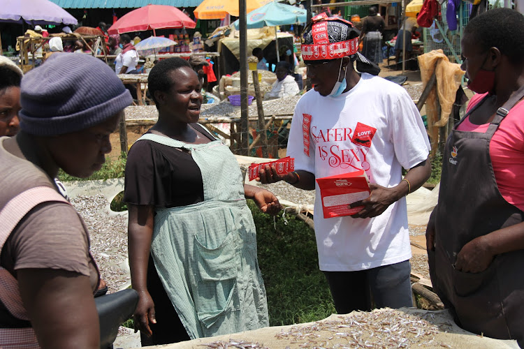 a member of Aids Healthcare Foundation distributes condoms to women fish sellers at Pier Beach in Homa Bay town on February 12/