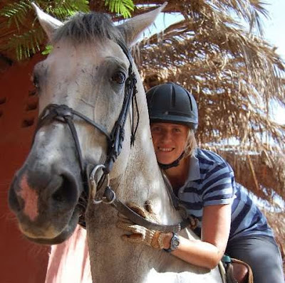 Krystal Kelly Horse Trainer Coach and Rider while working abroad in Egypt with horses poses with Obelix