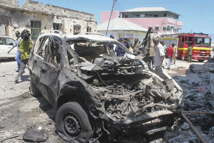 The remains of a destroyed car is seen at the scene of a car bomb attack. Picture: EPA/SAID YUSUF WARSAME