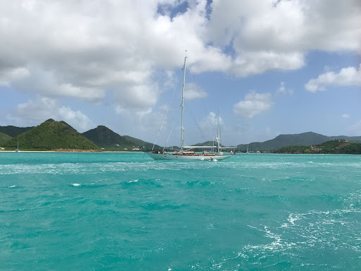 A sailboat plies the turquoise waters of Antigua.