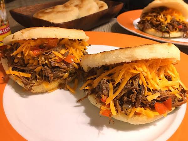 Two Arepas Filled With Beef Brisket And Shredded Cheddar Cheese On A White-orange Plate.
