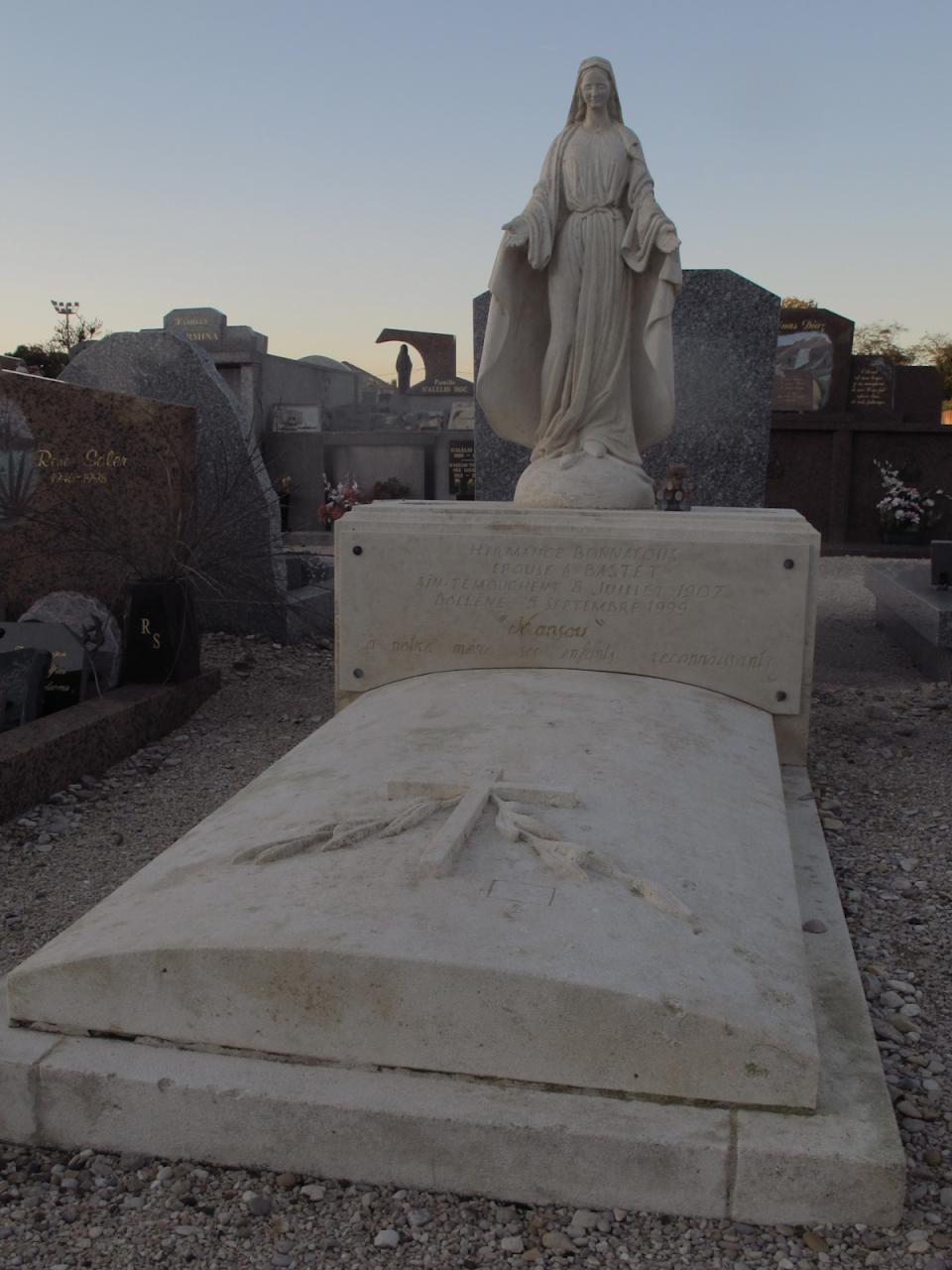 Tombe en pierre calcaire avec statue de sainte vierge et pierre tombale ornée