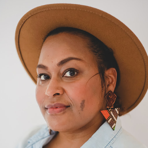 Portrait of artist in a caramel colored wool hat with orange and brown geometric shaped earrings.