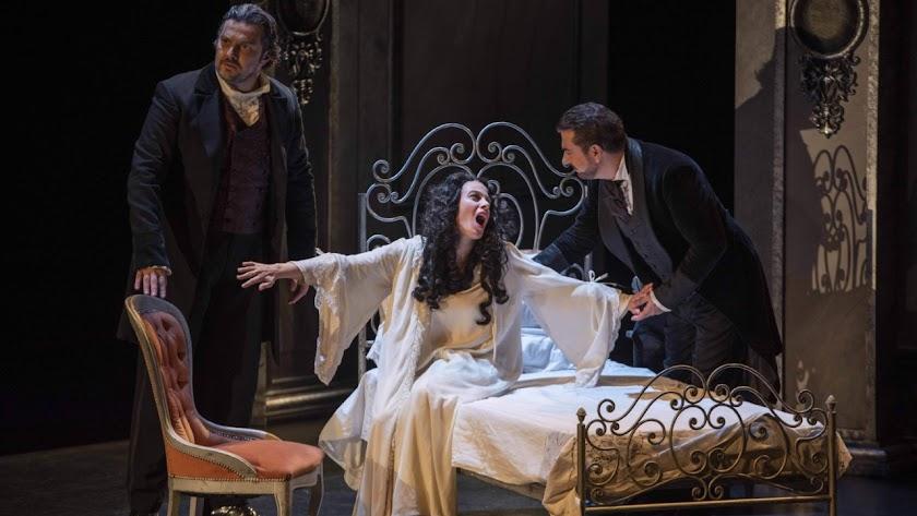 Violetta en su lecho de muerte, escuchada por Alfredo, en presencia de su padre.